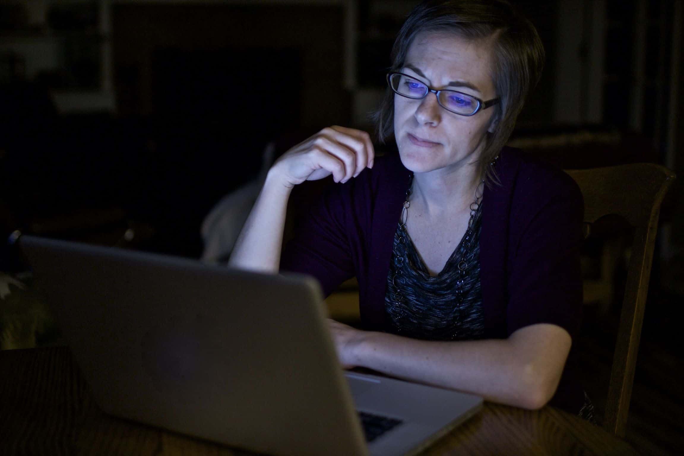 Frustrated woman working on laptop in the dark