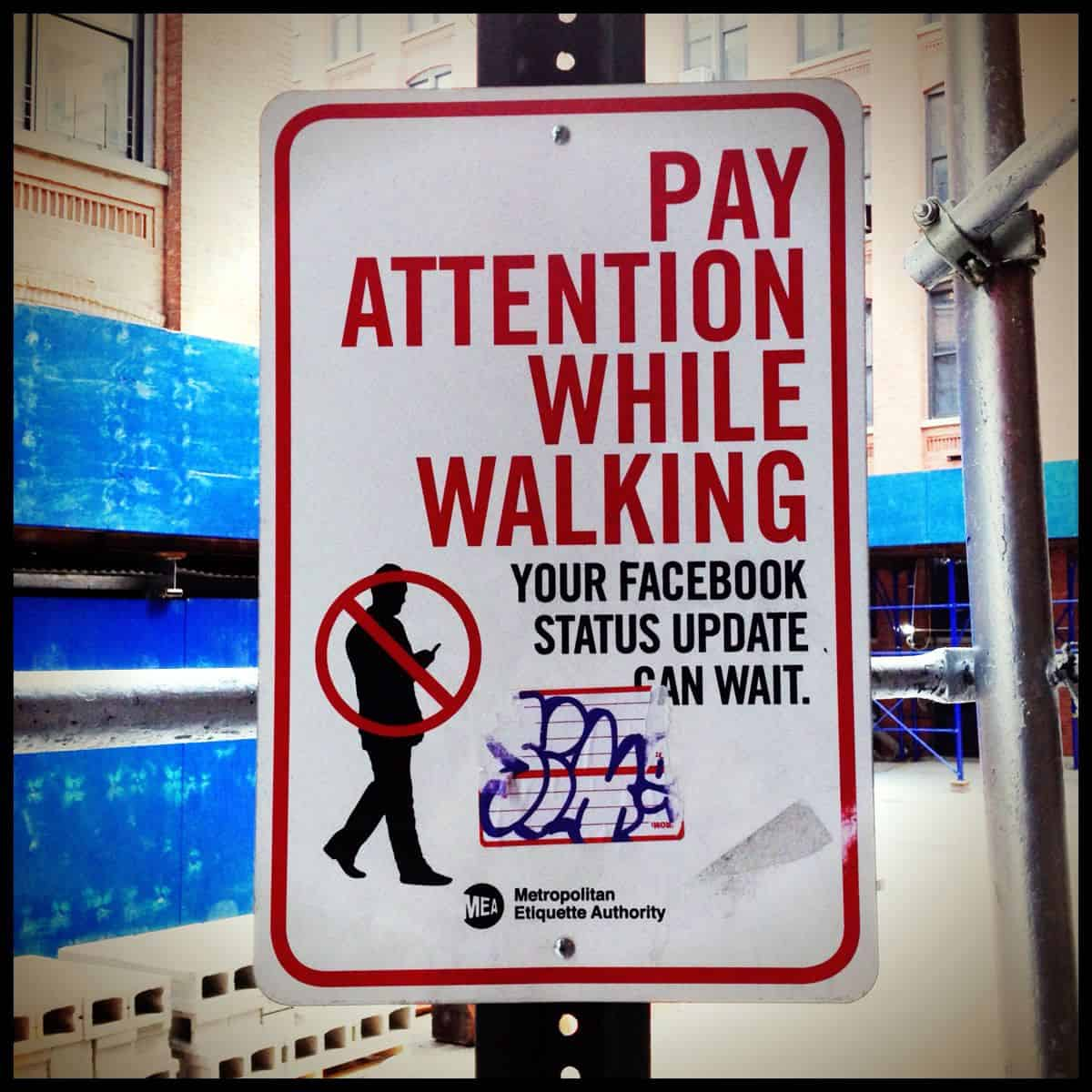 "A street sign shows the silhouette of a person walking while using his mobile phone, with the message, ""Pay attention while walking. Your Facebook status update can wait."""