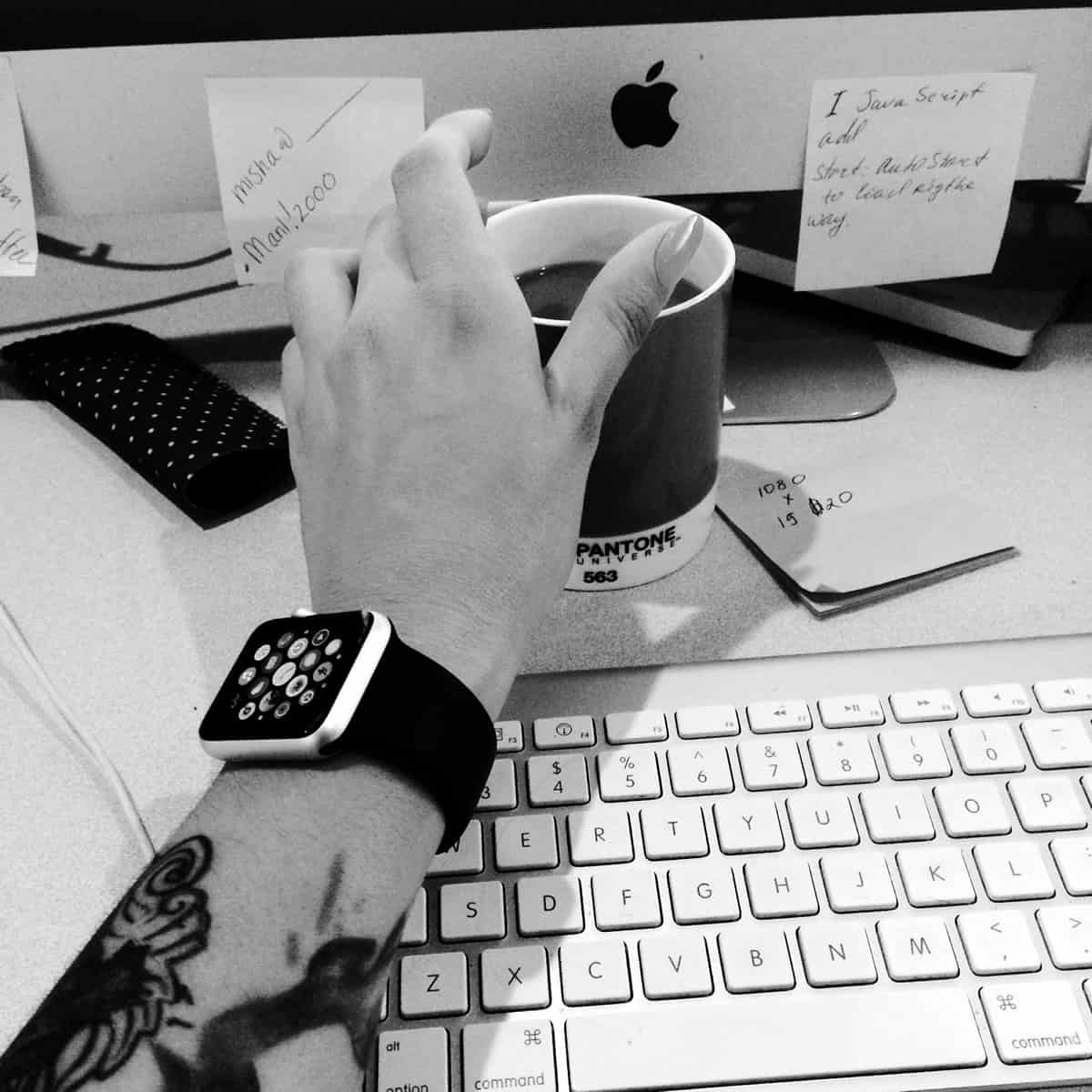 A black and white photo of a mobile app designer reaching for a coffee cup near an iMac monitor while wearing an Apple Watch.