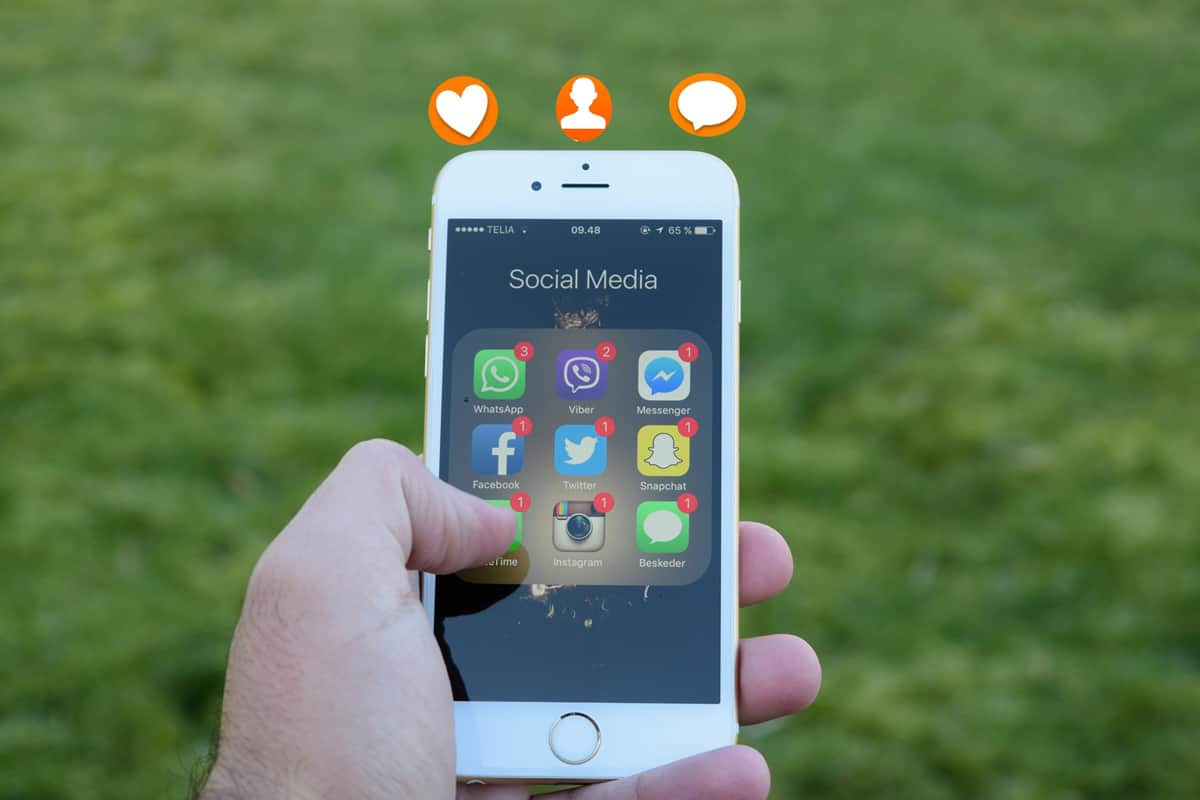 A photo of an iPhone displaying multiple social media app icons in a person's hand.