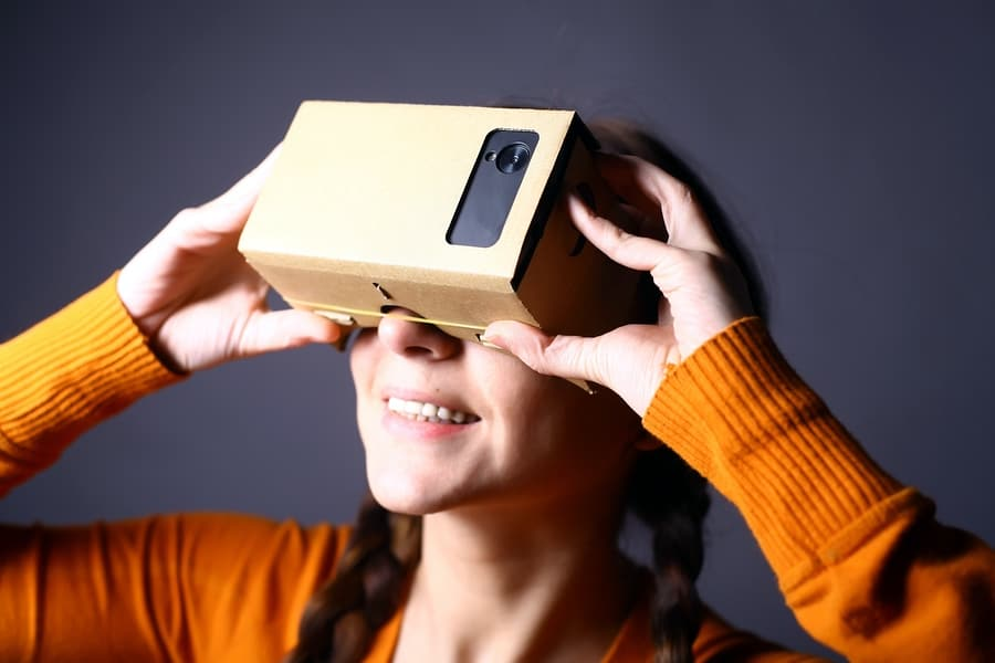 A photo of a smiling woman holding Google Cardboard up to her eyes.