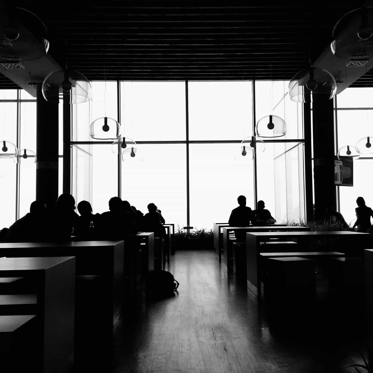 Image of people sitting on benches around tables.