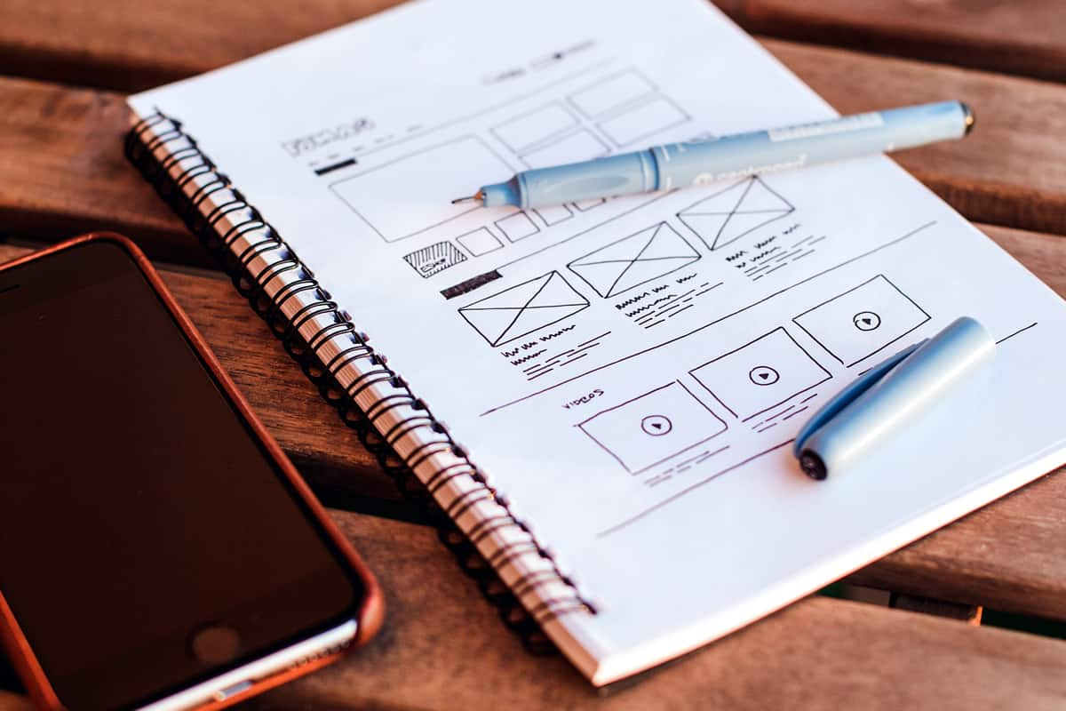 Image of a notebook and pen with a low fidelity wireframe.