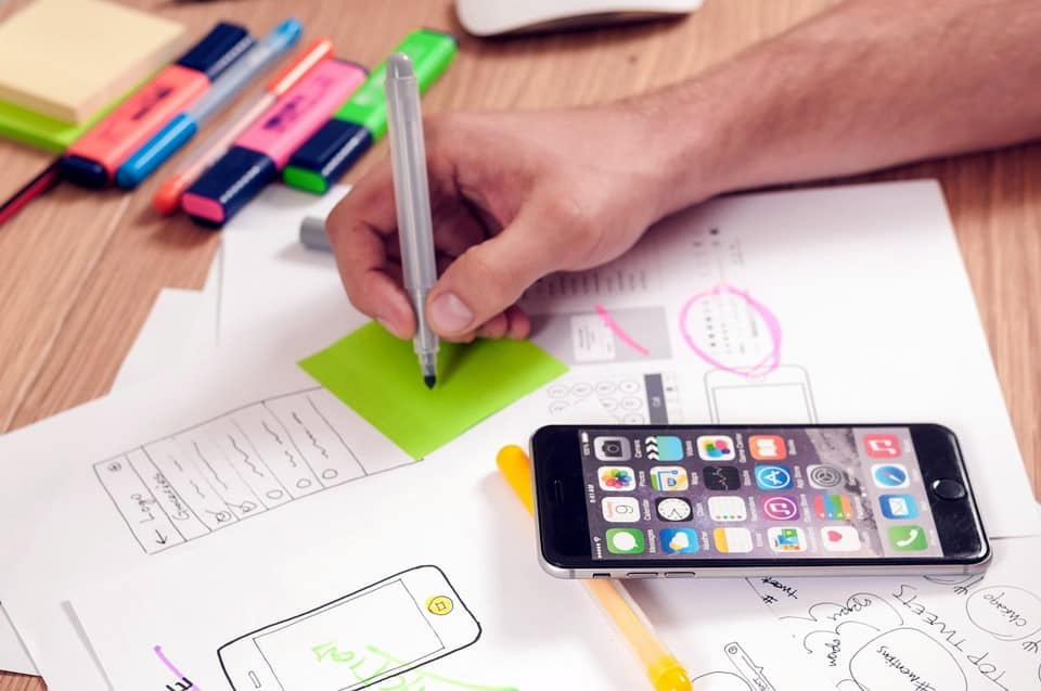 Image of a table, mobile phone and person sketching wireframes with a pile of papers on a table.
