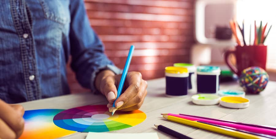 A photo of a mobile app designer using a color wheel to make palette decisions.