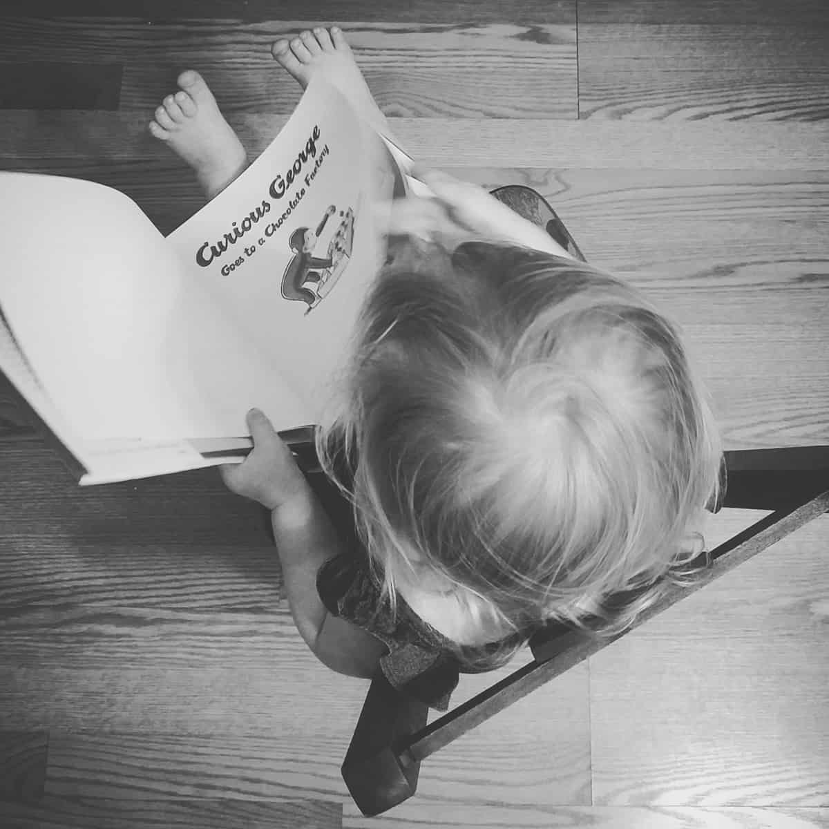 A photo of a child reading a Curious George book.
