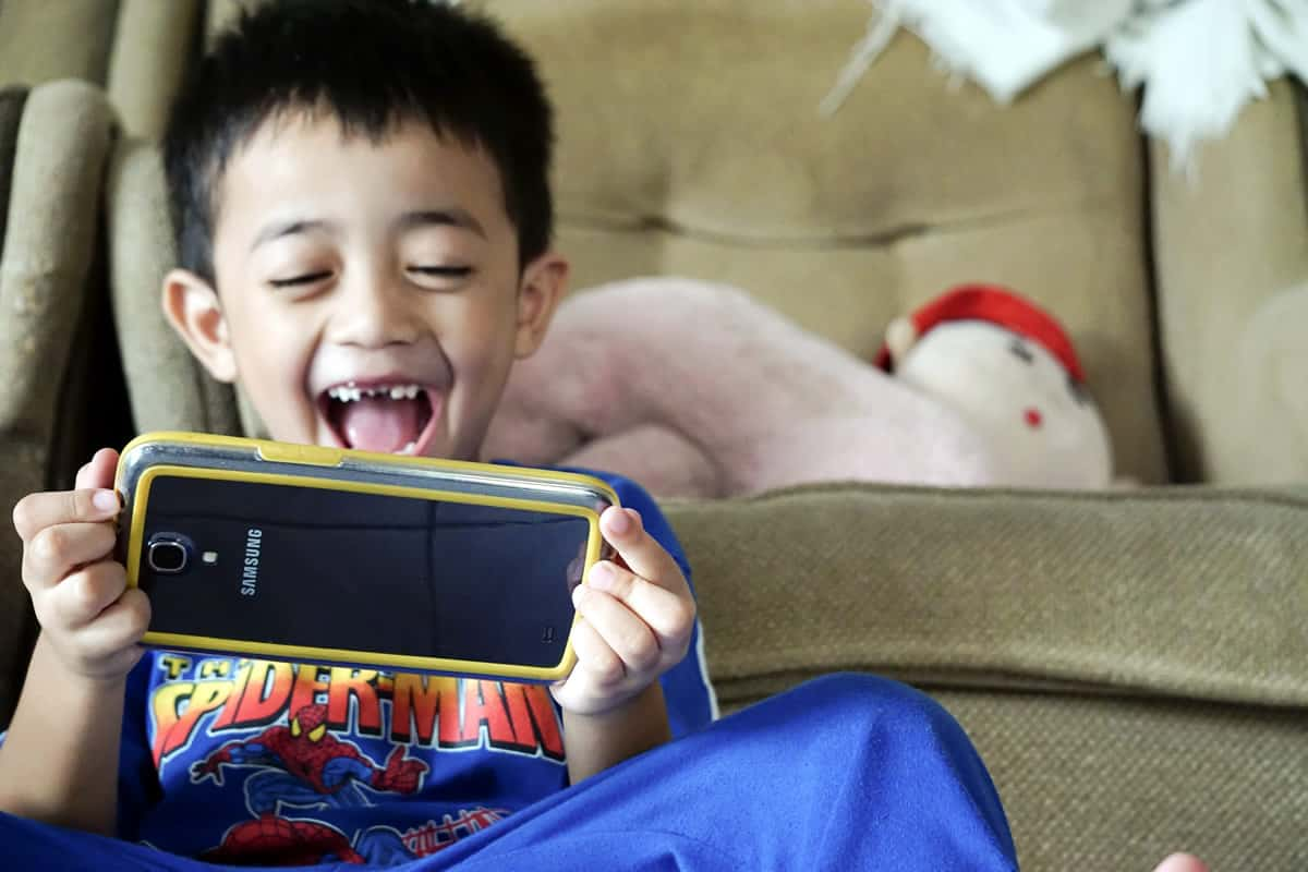 A photo of a happy child playing a game on a smartphone.