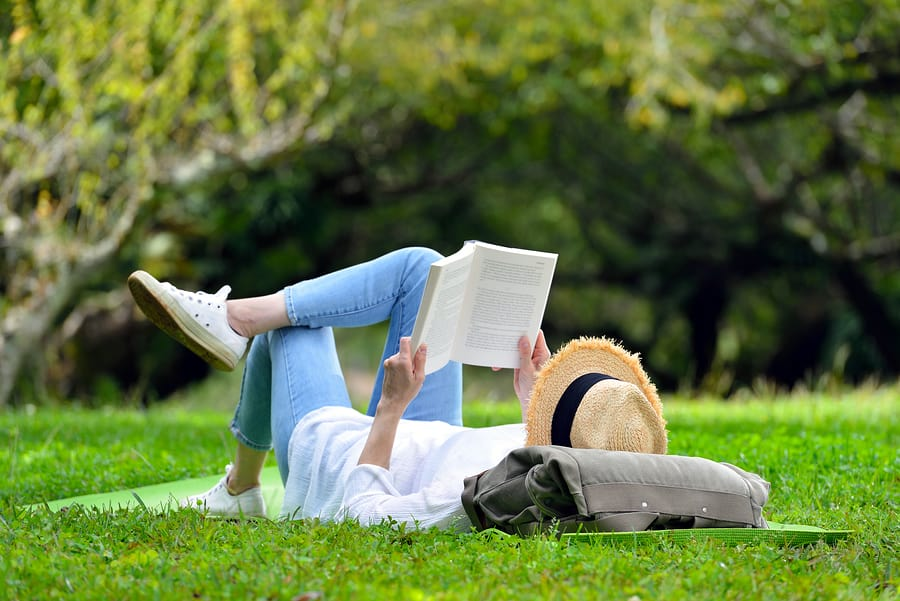 A photo of a woman lying in the grass and reading a book on a beautiful summer day.