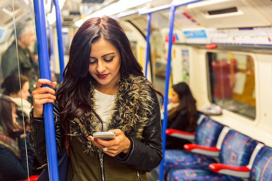 A photo of a woman looking at her smartphone while standing on the subway.