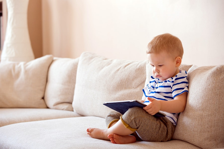 A photo of a child playing with a tablet on a couch.