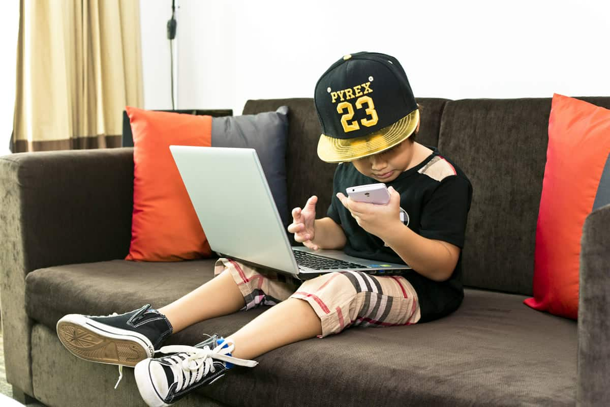A photo of a child sitting with a laptop in his lap and a smartphone in his hand.