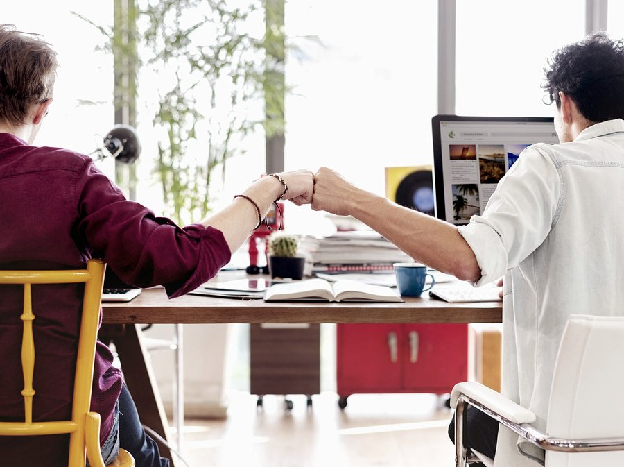 A photo of two coworkers fist bumping at their desks.