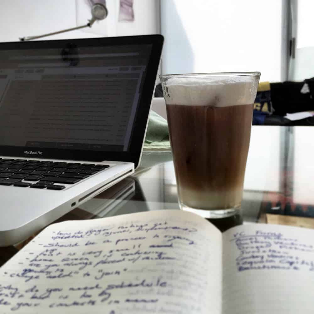 A photo of a journal full of to-dos next to a laptop and fresh latte.