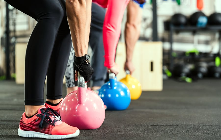 A photo of three people preparing for an exercise using heavy kettlebells.