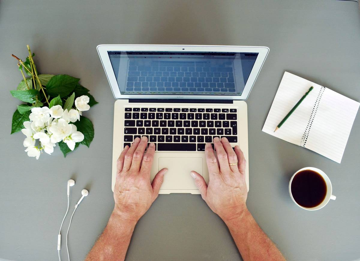 A photo of a man working on a laptop at his very clean, minimalist desk.