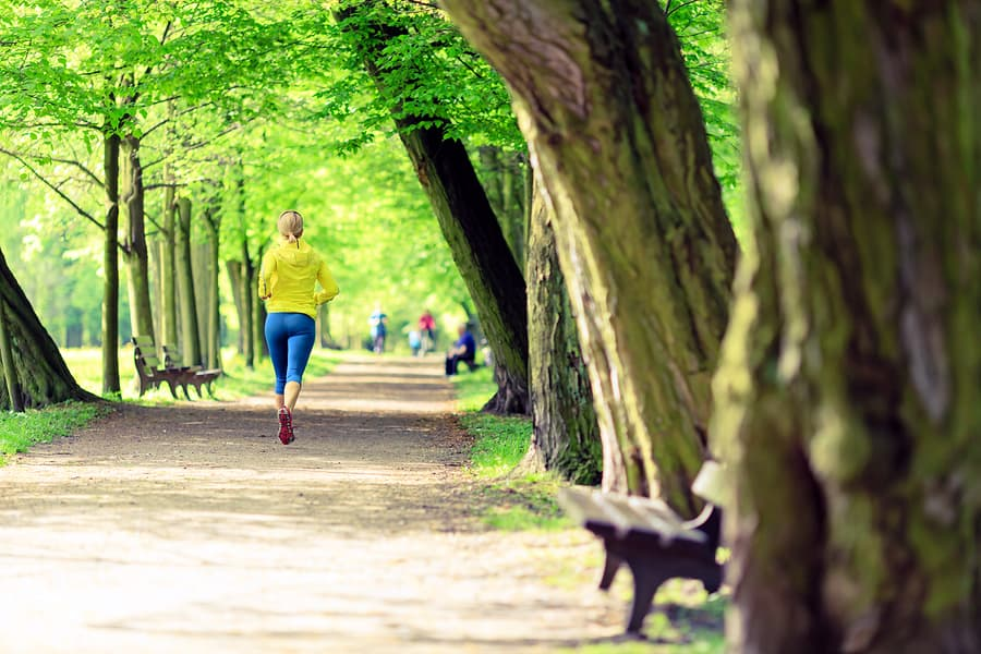 A photo of a woman running in the park on a beautiful spring day.