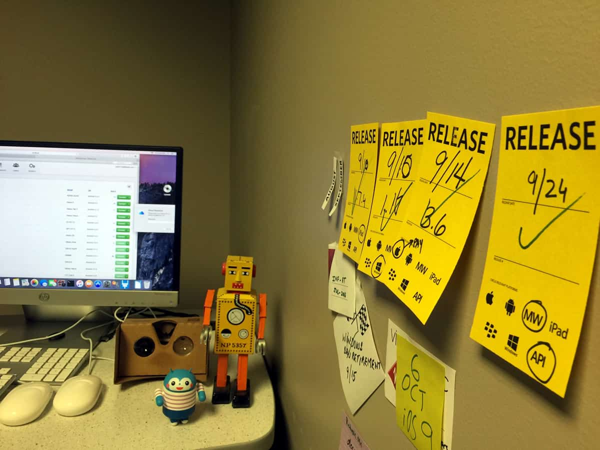 A photo of a person's office with multiple sticky notes hanging on the wall.