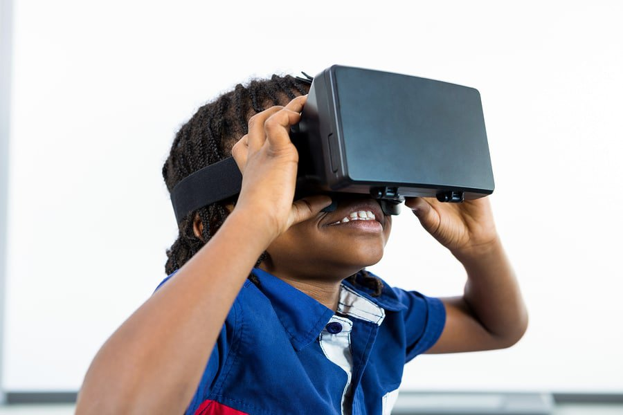 A photo of a child wearing a virtual reality headset with a big smile on his face.
