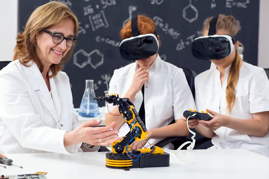 A photo of two students using virtual reality and a remote control to operate a robotic device in a classroom.