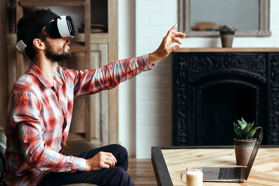 A photo of a man wearing a virtual reality headset and reaching out to touch something in front of him.