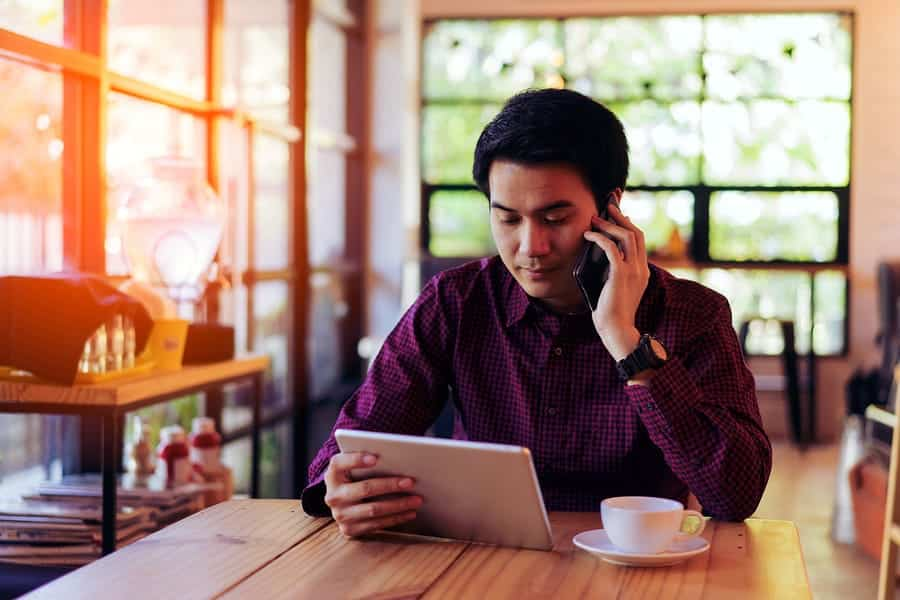 A man works while on his phone at a coffee shop.