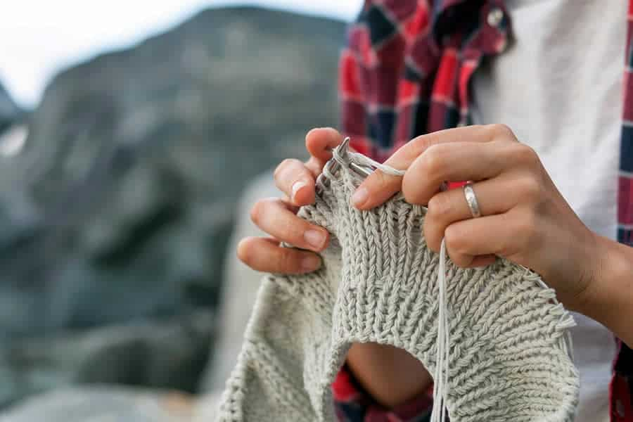 A close-up photo of a woman's hands knitting on circular needles.