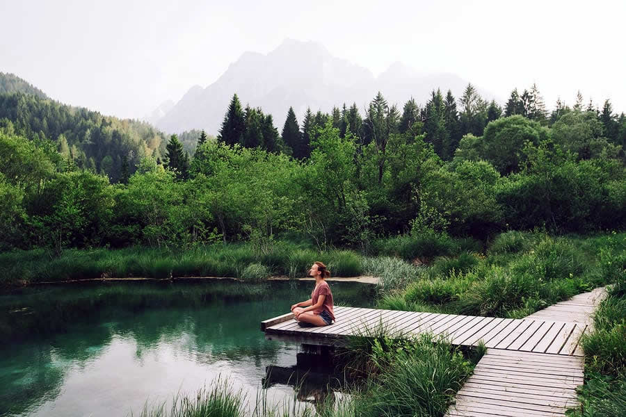 A photo of a person meditating at the end of a short dock on a pond.