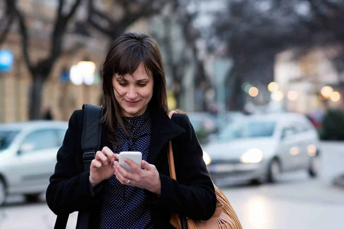 A photo of a woman walking down the street while looking at her smartphone.