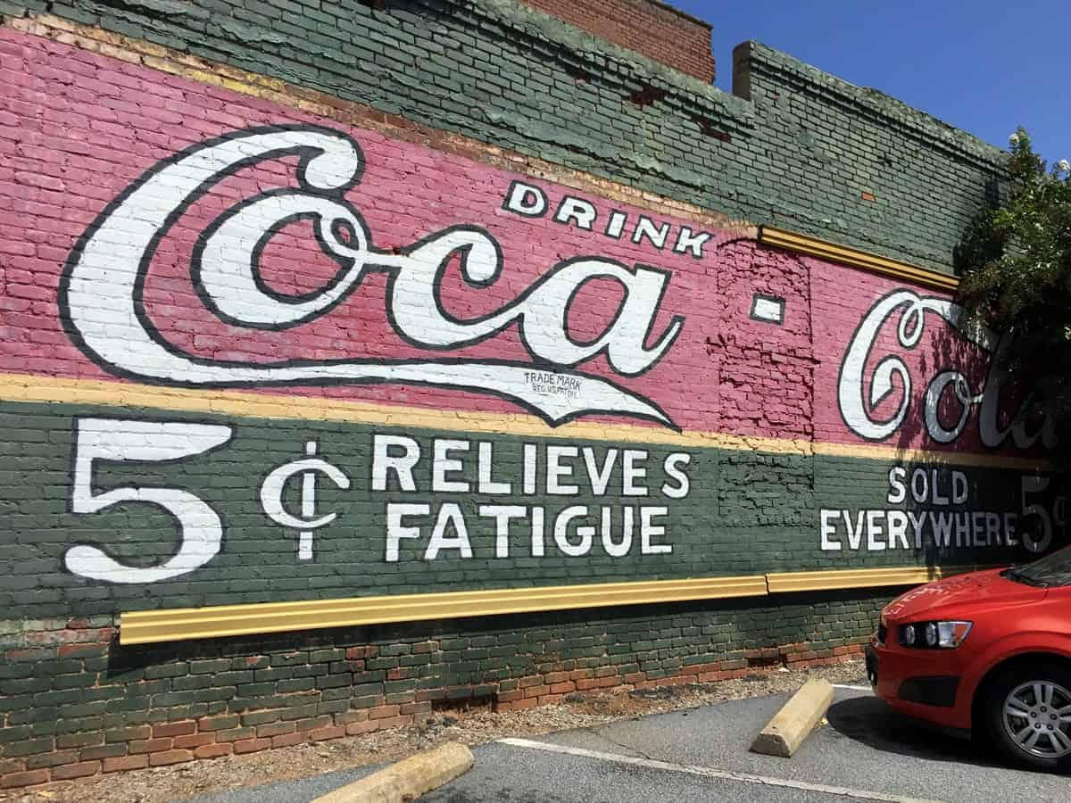 A photo of an old Coca-Cola ad painted on a brick building.