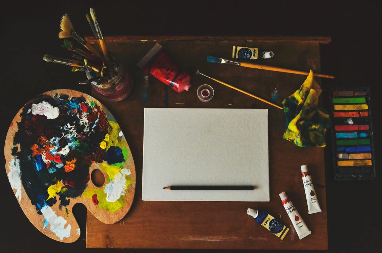 Paints, brushes, and other art supplies on a table.