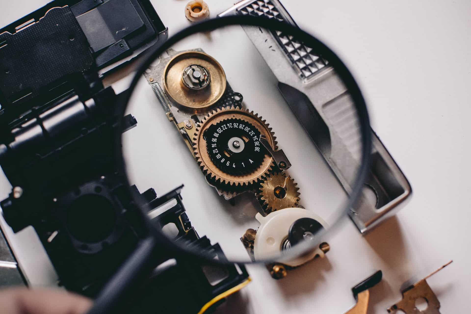 A magnifying glass showing intricate gears.