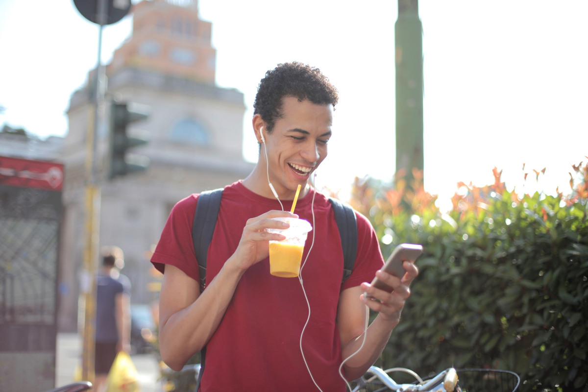 A smiling man walking down the street drinking juice and using his phone.