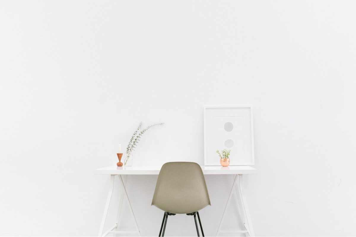A minimalist desk with a gray chair, two plants, and a piece of art.