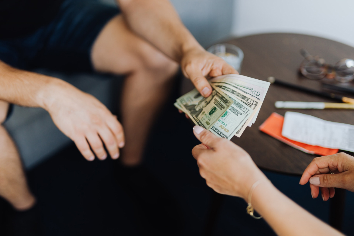 A person handing cash to someone.
