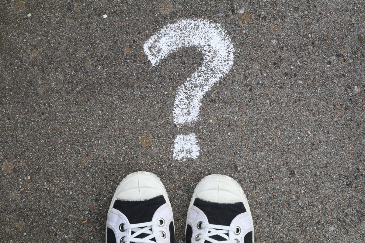 A question mark drawn on the ground with chalk and shoes.