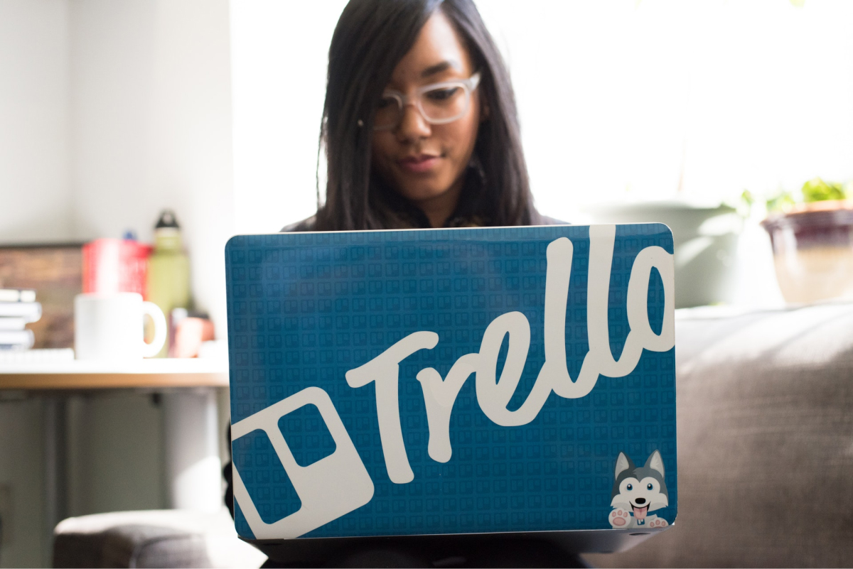 A woman working on a laptop that has a Trello case.
