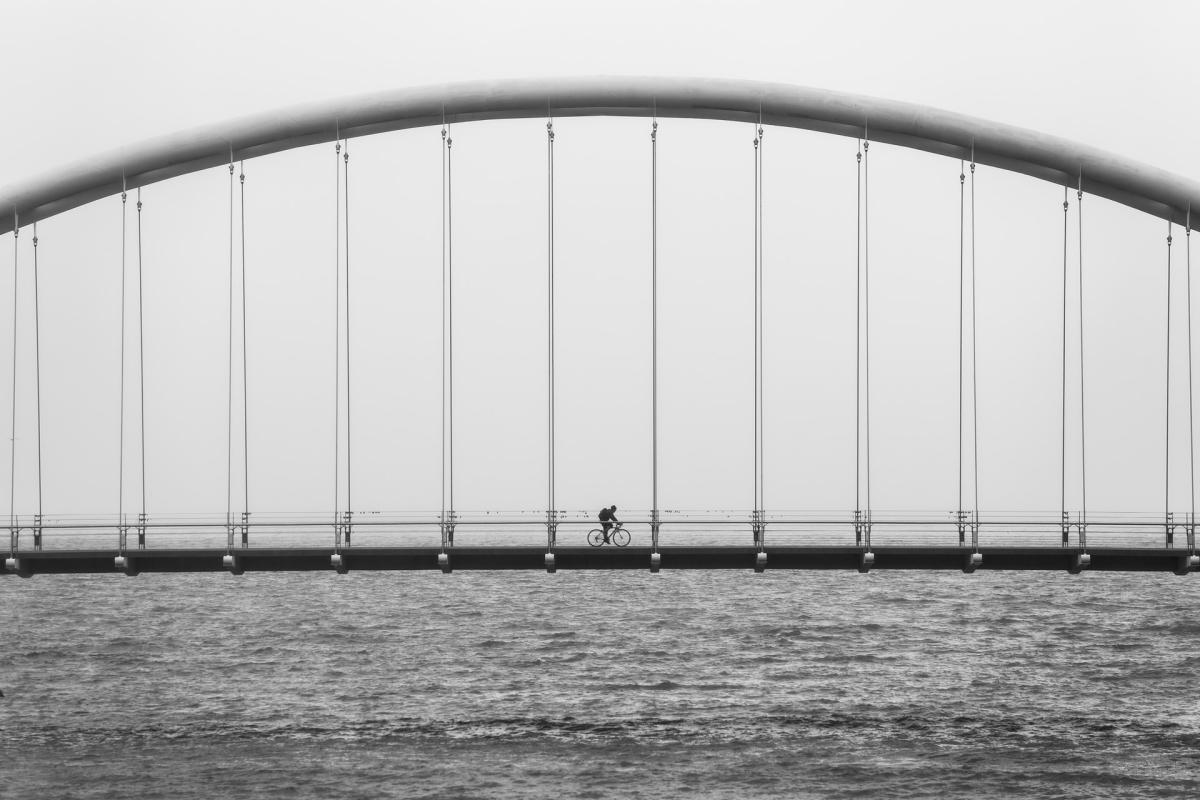 A person riding a bike over a bridge.